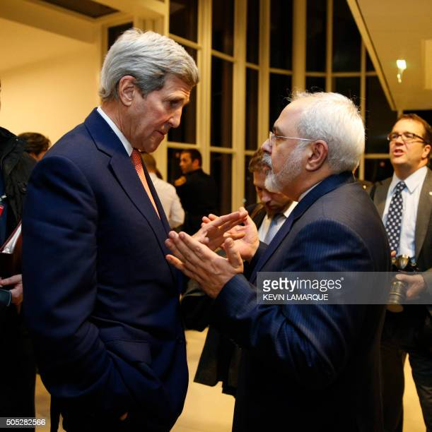 US Secretary of State John Kerry speaks with Iranian Foreign Minister Mohammad Javad Zarif after the International Atomic Energy Agency verified that...