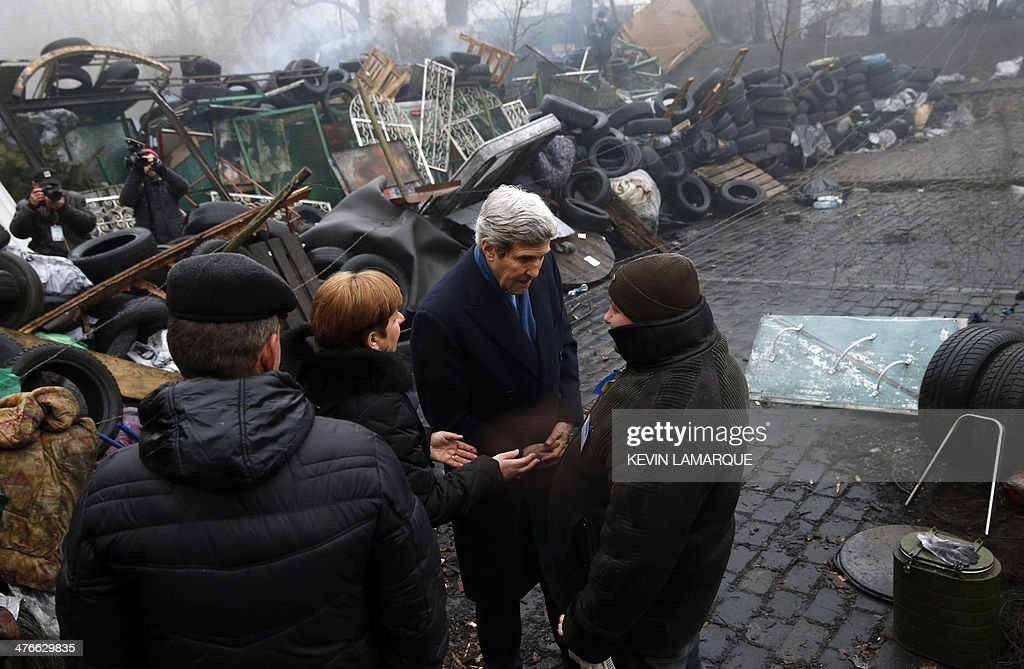 US Secretary of State John Kerry (2nd R) stands beside a barricade at the Shrine of the Fallen in Kiev on March 4, 2014. The Shrine of the Fallen, located on Institutska Street, honors the fallen 'Heroes' of the 'Heavenly Sotnya' (Hundred). Over the course of the EuroMaidan protests, almost 100 protesters were killed by police. Most of them died on February 20 killed by sniper or automatic weapons fire on Institutska Street. US Secretary of State John Kerry arrived in Kiev Tuesday for talks with Ukraine's new interim government, amid an escalating crisis in Crimea. His visit came as the United States said it would provide $1 billion to financially-stricken Ukraine as part of an international loan. With the Black Sea peninsula of Crimea under near complete control by pro-Russian forces, US officials said Moscow could face sanctions within days. AFP PHOTO / POOL - Kevin Lamarque