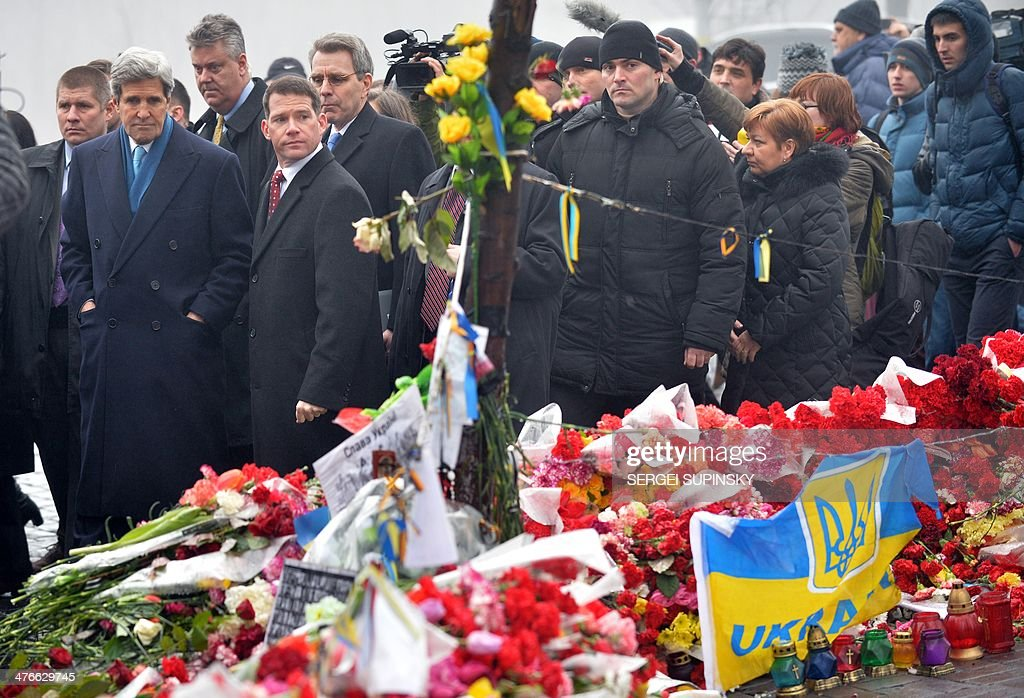 US Secretary of State John Kerry (2nd L) stands in front of the Shrine of the Fallen, an homage to anti-government protesters who died during the February clashes with anti-riot policemen in Kiev, on March 4, 2014. US Secretary of State John Kerry arrived in Kiev Tuesday for talks with Ukraine's new interim government, amid an escalating crisis in Crimea. His visit came as the United States said it would provide $1 billion to financially-stricken Ukraine as part of an international loan.