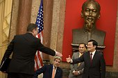 US Secretary of State John Kerry takes his seat while Vietnam's President Truong Tan Sang greets guests before a meeting at the Presidential Palace...