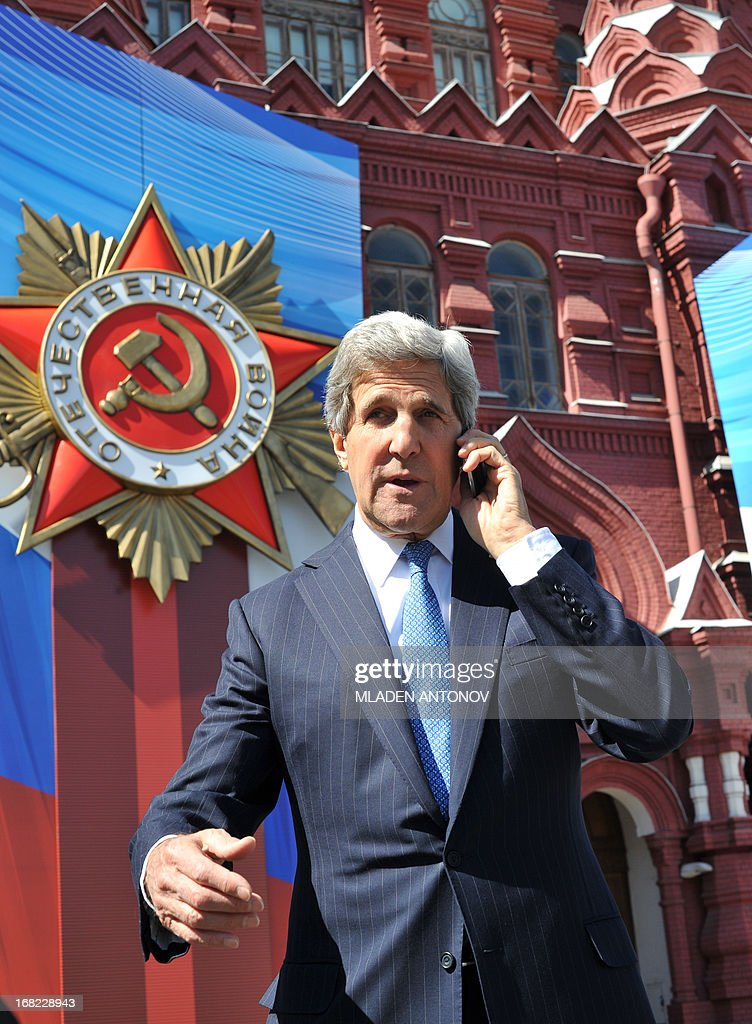 US Secretary of State John Kerry talks on a cell phone as he walks in front of a giant poster marking the upcoming Victory Day on the Red Square in Moscow on May 7, 2013. Kerry arrived today in Moscow for talks with Russian President Vladimir Putin, seeking to restore frayed US-Russia ties and win Moscow's support on the war in Syria. AFP PHOTO/POOL/MLADEN ANTONOV