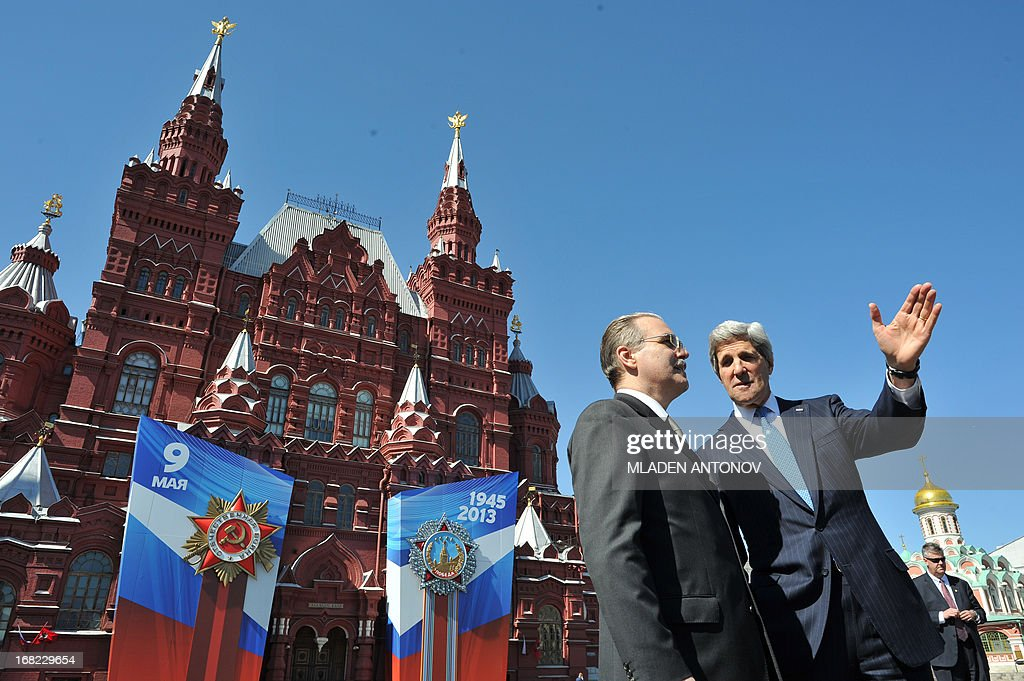 US Secretary of State John Kerry talks (R) talks to Yuri Filatov from the Russian Foreign Ministry during a walk at the Red Square in Moscow on May 7, 2013, with a huge poster (back) to mark the upcoming Victory Day. Kerry arrived today in Moscow for talks with Russian President Vladimir Putin, seeking to restore frayed US-Russia ties and win Moscow's support on the war in Syria.