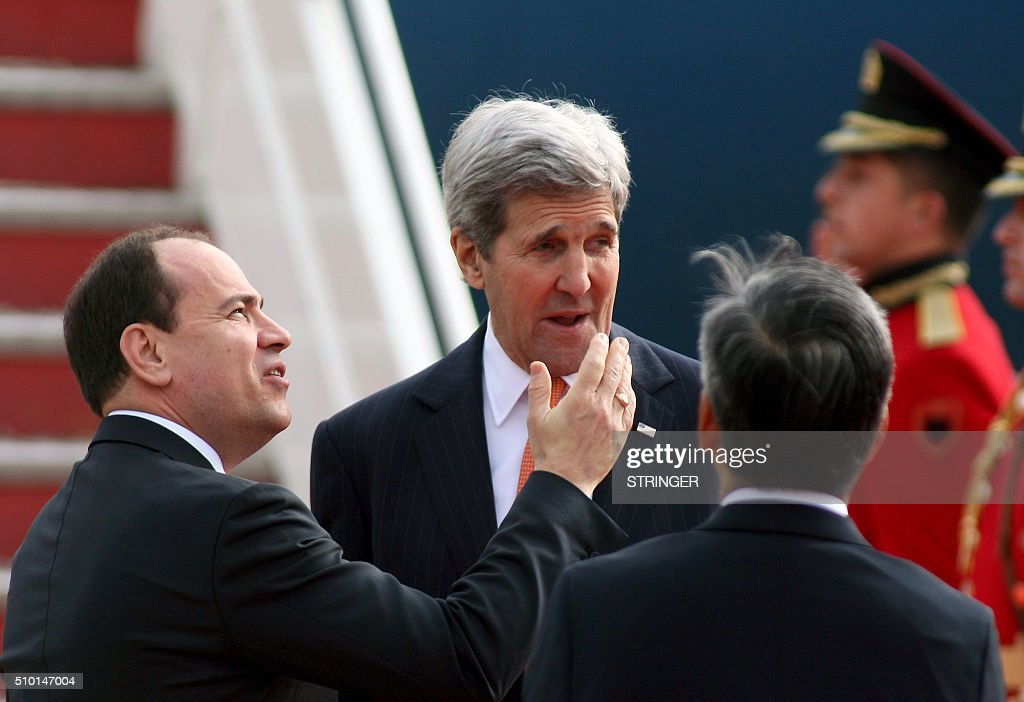 US Secretary of State John Kerry (C) talks with Albanian President Bujar Nishani (L) during a welcoming ceremony at Mother Teresa airport in Tirana on February 14, 2016. US Secretary of State is in a few hours visit to Tirana, to meet with senior government leaders to discuss Albania's further Euro-Atlantic integration and strong bilateral cooperation with the United States. / AFP / STRINGER