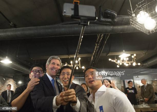 US Secretary of State John Kerry uses a 'selfie stick' to take a photograph with Sid Kim Juweon Jonathan Kim and Kenny Park owners of Vatos Urban...