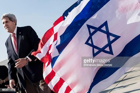 US Secretary of State John Kerry walks past American and Israeli flags at Ben Gurion International Airport in Tel Aviv on January 6 2014 Kerry is...