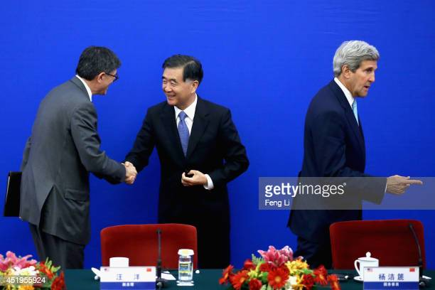 S Secretary of State John Kerry walks past as China's Vice Premier Wang Yang shakes hands with US Secretary of the Treasury Jack Lew after a press...
