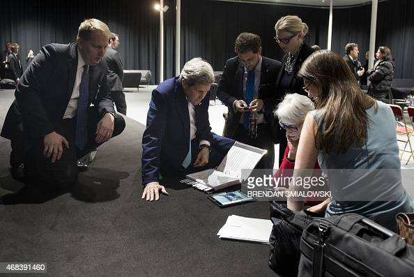 US Secretary of State John Kerry watches on a tablet as the US president addresses the US at the Swiss Federal Institute of Technology in Lausanne on...