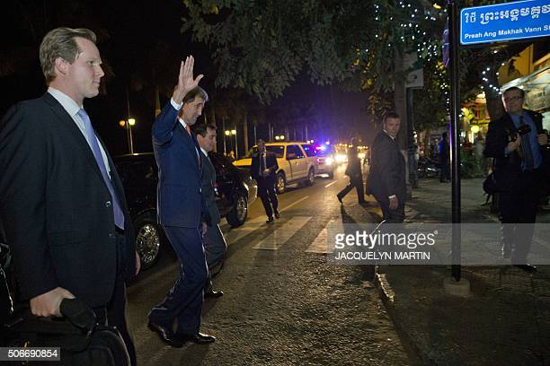 US Secretary of State John Kerry waves to the crowd as he crosses a street on the waterfront in Phnom Penh after arriving in Cambodia on January 25...