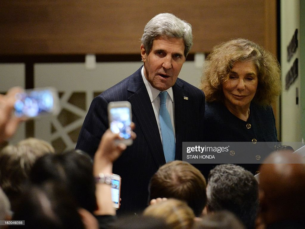 US Secretary of State John Kerry (C) with wife Teresa Heinz (R) walks past the media outside the United Nations Security Council just after the Council voted to approve a resolution that will require Syria to give up its chemical weapons during a meeting September 27, 2013 at UN headquarters in New York. AFP PHOTO/Stan HONDA