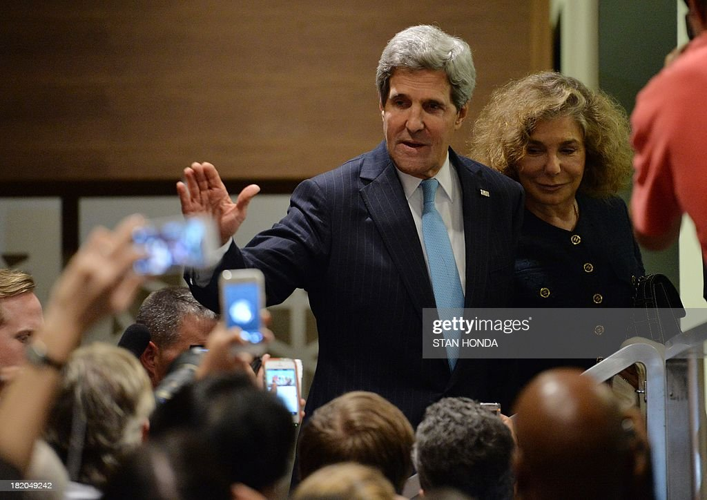 US Secretary of State John Kerry (C) with wife Teresa Heinz (R) waves to the media outside the United Nations Security Council just after the Council voted to approve a resolution that will require Syria to give up its chemical weapons during a meeting September 27, 2013 at UN headquarters in New York. AFP PHOTO/Stan HONDA