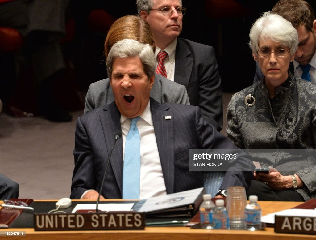 US Secretary of State John Kerry yawns as he listens to speakers in the Security Council just after the Council voted to approve a resolution that will require Syria to give up its chemical weapons during a meeting September 27, 2013 at UN headquarters in New York. AFP PHOTO/Stan HONDA