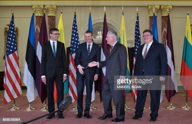 US Secretary of State Rex Tillerson reaches out to shake hands with Estonian Foreign Minister Sven Mikser watched by Latvian Foreign Minister Edgars...