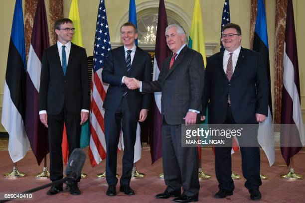 US Secretary of State Rex Tillerson shakes hands with Latvian Foreign Minister Edgars Rinkevics watched by Estonian Foreign Minister Sven Mikser and...