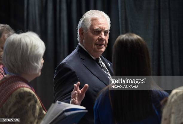 US Secretary of State Rex Tillerson speaks with a delegate as he visits the Working Group Exhibition at the Arctic Council meeting in Fairbanks...