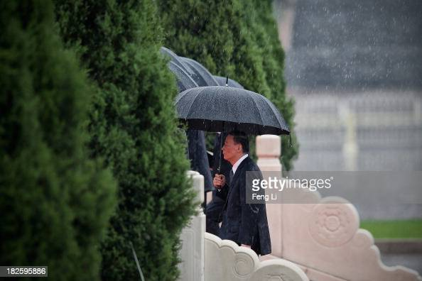 Secretary of the Central Commission for Discipline Inspection Wang Qishan and Chinese Communist Party top leaders hold their umbrellas in the rain as...