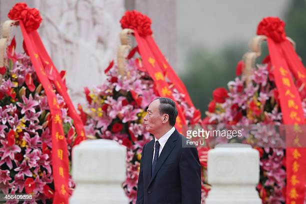 Secretary of the Central Commission for Discipline Inspection Wang Qishan walks past the Monument to the People's Heroes during a ceremony marking...