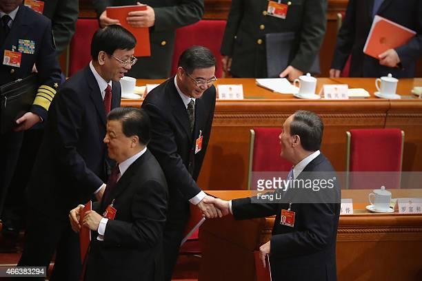 Secretary of the Central Commission for Discipline Inspection Wang Qishan shakes hands with President of Supreme People's Court of China Zhou Qiang...