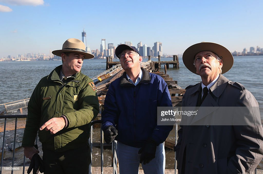 U.S. Secretary of the Interior Ken Salazar (C), looks to the Statue of Liberty which, remains closed to the public six weeks after Hurricane Sandy on December 13, 2012 in New York City. The storm caused extensive damage to National Park Service facilities on Liberty Island, although the statue itself remained unscathed, according to Salazar.