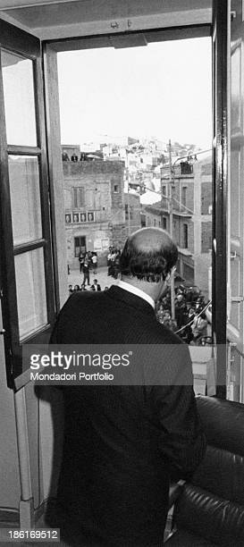 Secretary of the Italian Socialist Party Bettino Craxi looking out through the window of a house in his native town San Fratello 1980s