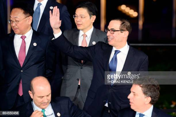 US Secretary of the Treasury Steven Mnuchin waves as he and other participants in the G20 Finance Ministers and Central Bank Governors Meeting pose...
