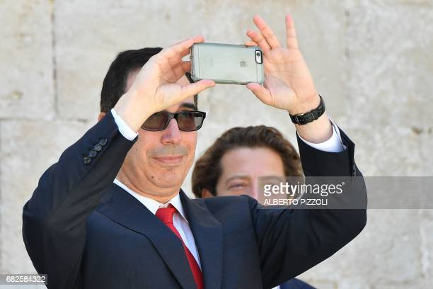US Secretary of Treasury Steven Mnuchin snaps a picture with his smartphone at the end of a G7 summit of Finance Ministers on May 13 2017 in Bari G7...