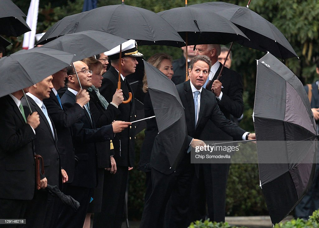 S Secretary of Treasury Timothy Geithner tries shake water from his umbrella before the start of an arrival ceremony for President Lee Myungbak of...