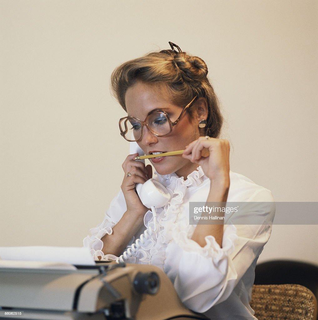 Secretary on telephone biting pencil