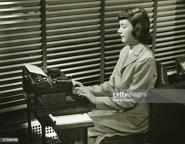 Secrétaire dactylographie sur machine à écrire dans le bureau (B & W