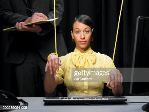 Secretary with hands tied in strings, businessman in background