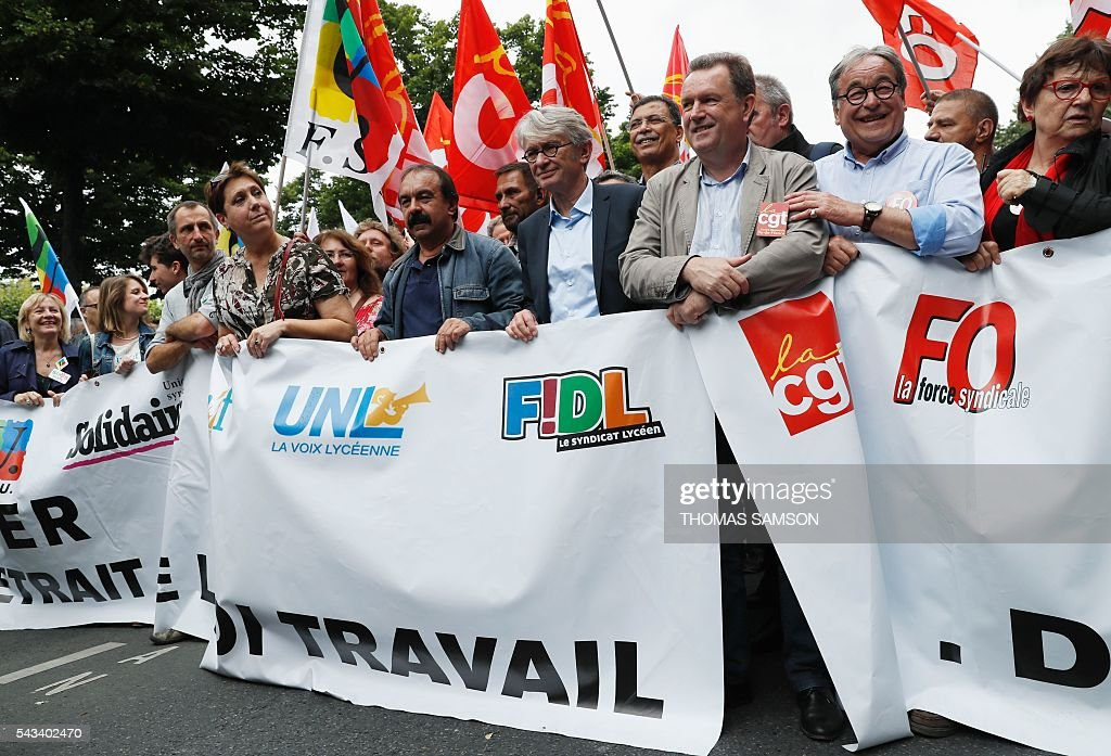 Secretary-general of the French General Confederation of Labour (CGT) Philippe Martinez (C-L) and Secretary-general of the French worker's union Force Ouvriere (FO) Jean-Claude Mailly (C-R) hold a banner during a demonstration against the series of controversial labour reforms on June 28, 2016 in Paris. / AFP / Thomas SAMSON