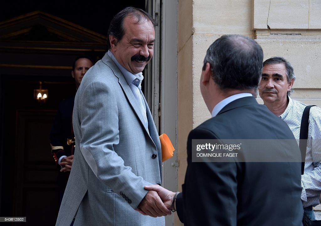 Secretary-general of the French General Confederation of Labour (CGT) Philippe Martinez (L) shakes hands with CFTC union general secretary Laurent Berger as he arrives at the Hotel Matignon in Paris on June 29, 2016 before a meeting on the Socialist government's labour reforms with French Prime minister and French Labour minister. / AFP / DOMINIQUE