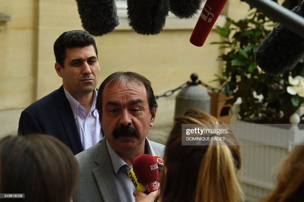 Secretary-general of the French General Confederation of Labour (CGT) Philippe Martinez (R) answers journalists' questions at the Hotel Matignon in Paris on June 29, 2016 after a meeting on the Socialist government's labour reforms with French Prime minister and French Labour minister. / AFP / DOMINIQUE