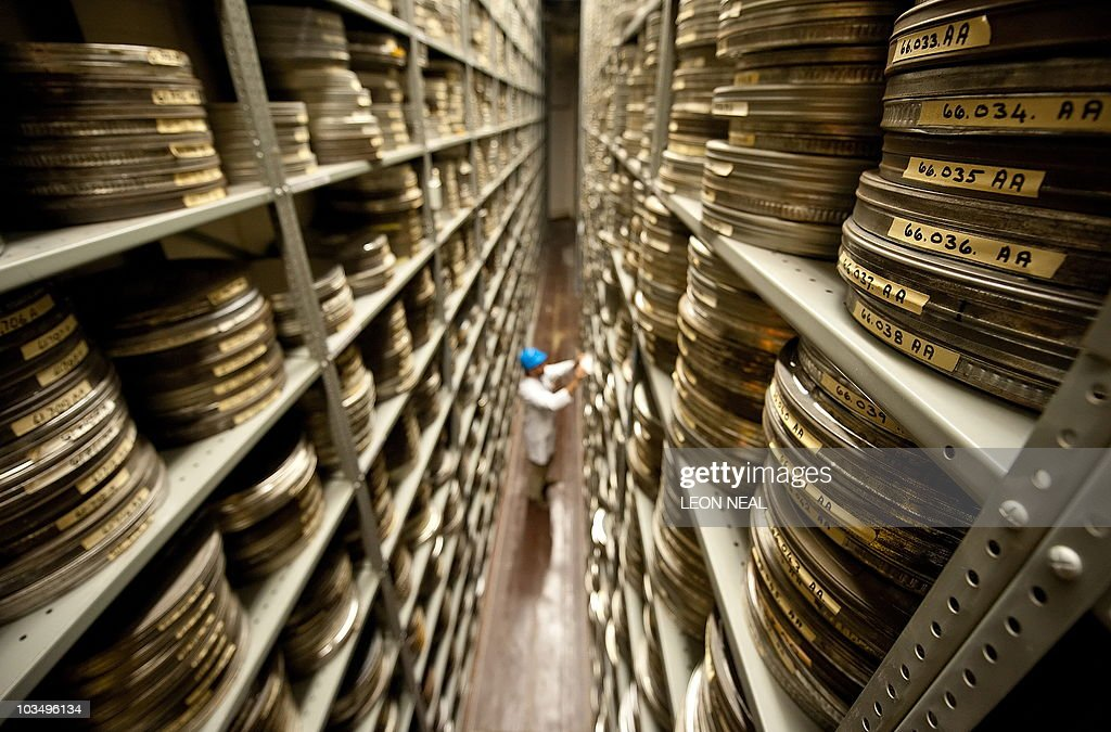 Section Leader for Image Quality, Ben Thompson, looks at film canisters within the acetate vault at the BFI (British Film Institute) film archive in Berkhamsted, Hertfordshire on July 23, 2010. Examining buckled film reels under a microscope, technicians pore over each precious original frame of Alfred Hitchcock's early movies as Britain bids to salvage the master's magic. The delicate nitrate reel -- brown, brittle and shrunken -- is handled with extreme care as they scrutinise the opening credits of the 1927 film 'The Lodger' for every miniscule scratch, blotch and speck. The British Film Institute is undertaking a mammoth project to restore Hitchcock's silent movies to their former glory. Photo taken July 23, 2010. AFP PHOTO/Leon Neal