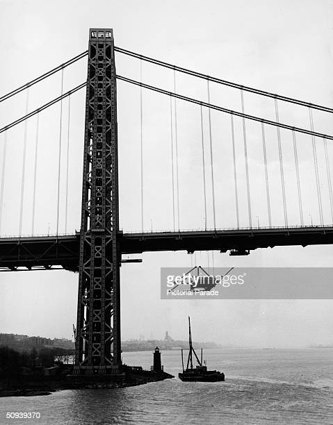 A section of steel is hoisted from a barge during construction of the lower level of the George Washington Bridge New York City 1960