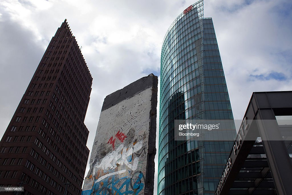 A section of the Berlin Wall stands near Deutsche Bahn AG's headquarters, second right, in Berlin, Germany, on Sunday, March 3, 2013. Germany's 10-year government bonds advanced for a second day even before a report that economists said will show producer prices in the euro area increased for the first time in four months in January. Photographer: Krisztian Bocsi/Bloomberg via Getty Images