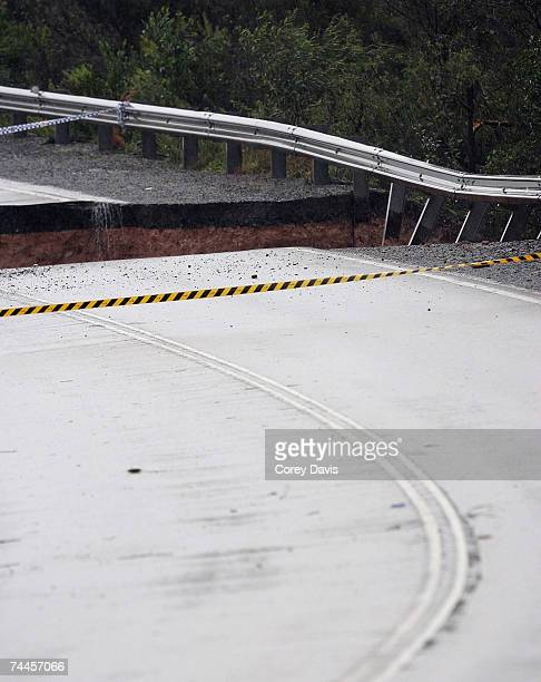 A section of the Old Pacific Highway is cordoned off after a family of five people were swept away in their car when the road collapsed June 9 2007...