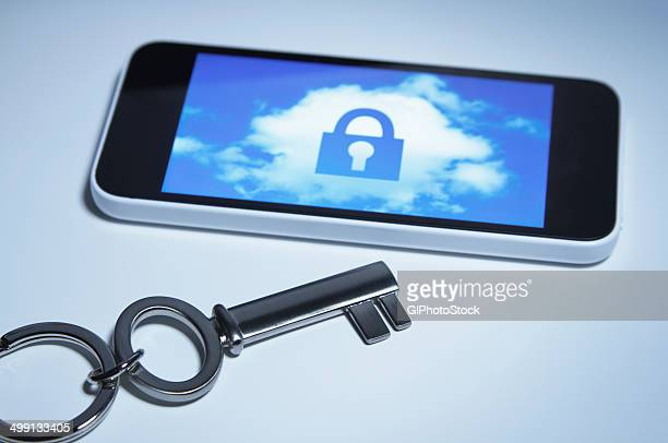 Secure smart phone. A key next to smartphone with a lock over a cloud on its screen.