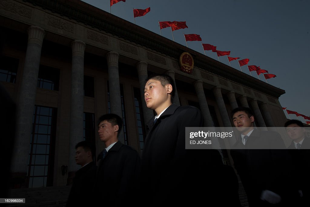 Securitry guards walk past the venue of the opening session of the Chinese People's Political Consultative Conference (CPPCC) at the Great Hall of the People in Beijing on March 3, 2013. Thousands of delegates from across China meet this week to seal a power transfer to new leaders whose first months running the Communist Party have pumped up expectations with a deluge of propaganda. AFP PHOTO / Ed Jones