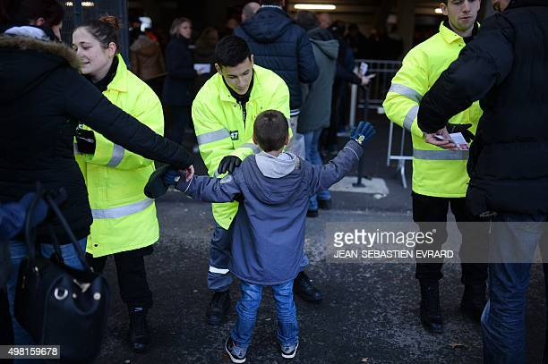 A security agent controls a young supporter outside the Moustoir stadium in Lorient western France as supporters arrive for the L1 football match...