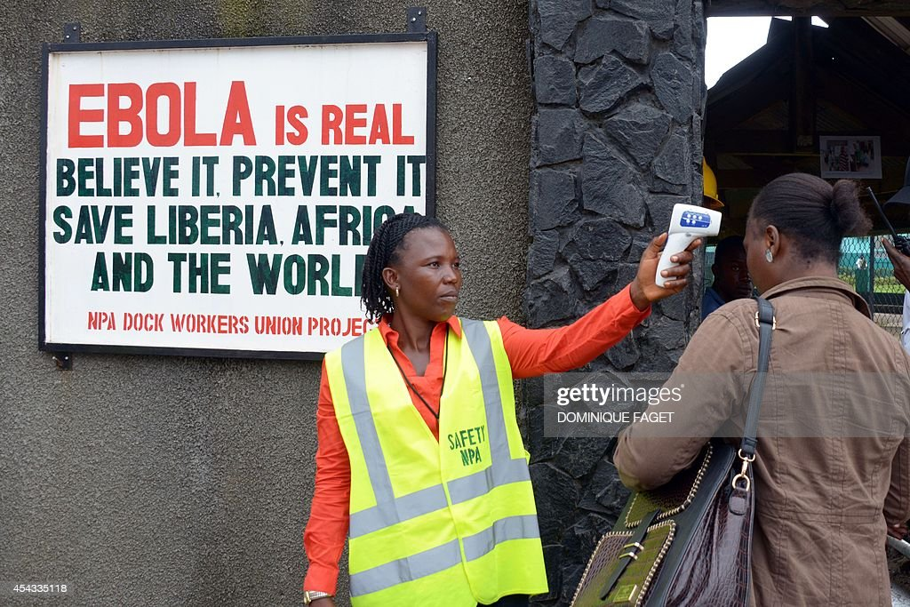 A security agent controls the temperature of a woman at the entrance of the port of Monrovia on August 29, 2014. The World Health Organization said yesterday that the number of Ebola cases was increasing rapidly and could exceed 20,000 before the virus is brought under control, as the death toll topped 1,500.