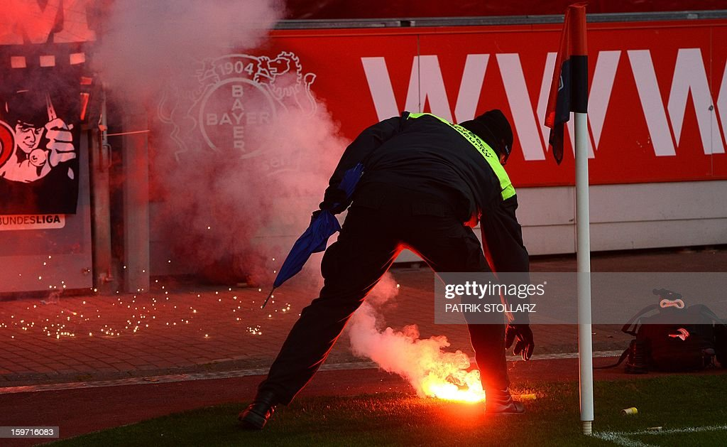 A security agent picks up a flare thrown down by hooligans during the German first division Bundesliga football match Bayer Leverkusen vs Eintracht Frankfurt in the German city of Leverkusen on January 19, 2013.