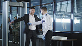 Airport security agent using a metal detector on a male passenger in a suit to pat him down at the boarding gate after passing through the x-ray scanner.