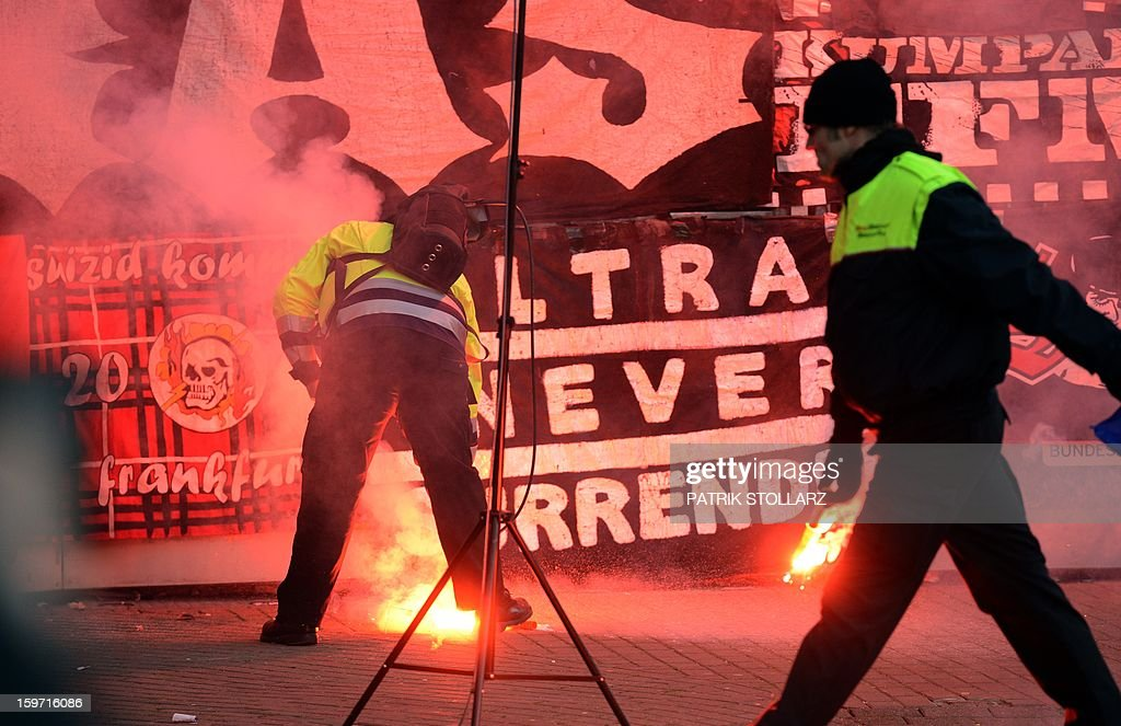 Security agents pick up flares thrown down by hooligans during the German first division Bundesliga football match Bayer Leverkusen vs Eintracht Frankfurt in the German city of Leverkusen on January 19, 2013. AFP PHOTO / PATRIK STOLLARZ