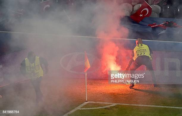 Security agents remove flares from the pitch during the Euro 2016 group D football match between Czech Republic and Turkey at BollaertDelelis stadium...