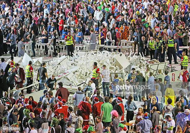 Security and police officers stand guard around a pile of plastic chairs and tables after spectators threw them during the final between Simon The...