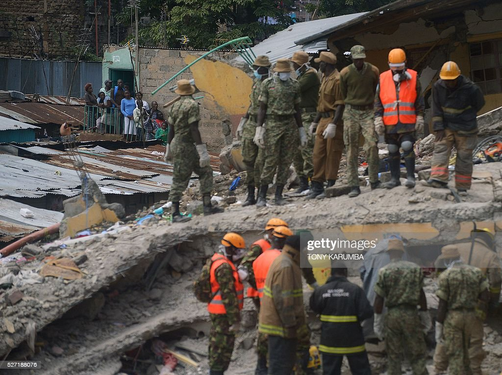 Security and rescue personel search for bodies trapped in rubble on May 2, 2016 at the scene of a collapsed residential building in the low-income suburb of Huruma in Nairobi. The death toll in the collapse of a six-storey building in Nairobi on April 29 rose to 21 on May 2 after four more bodies were pulled from the rubble of the residential structure that gave way during weekend storms. / AFP / TONY