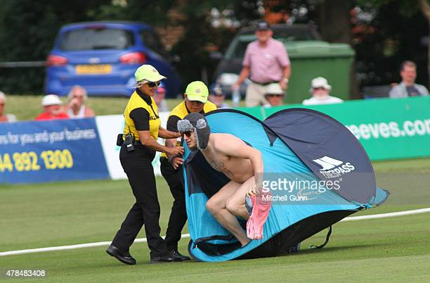 Security attempt to remove a fan with a tent who invaded the field of play during day one of the tour match between Kent and Australia at The...