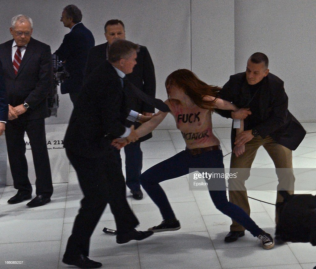 Security block an attack by an activist of the Ukrainian women rights group 'Femen' as Russian President <a gi-track='captionPersonalityLinkClicked' href=/galleries/search?phrase=Vladimir+Putin&family=editorial&specificpeople=154896 ng-click='$event.stopPropagation()'>Vladimir Putin</a> and German Chancellor Angela Merkel visit the industrial exhibition 'Hannover Messe' on April 8, 2013 in Hannover, Germany. More than 100 Russian companies are exhibiting their industrial productions.