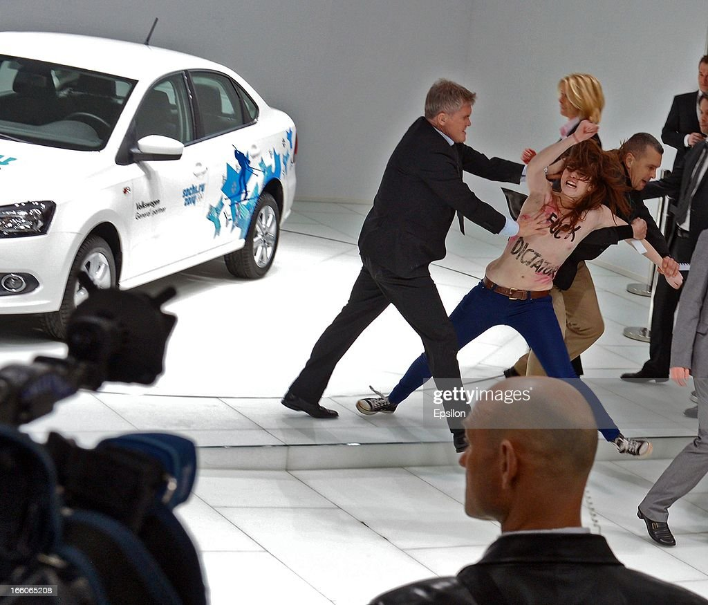 Security block an attack by an activist of the Ukrainian women rights group 'Femen' as Russian President Vladimir Putin and German Chancellor Angela Merkel visit the industrial exhibition 'Hannover Messe' on April 8, 2013 in Hannover, Germany. More than 100 Russian companies are exhibiting their industrial productions.