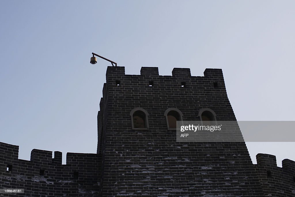 A security camera hangs on the outer corner of a mini replica of the Great Wall in Beijing World Park, in the southwestern suburb of Beijing on November 23, 2012. Beijing World Park, with a collection of mini replicas of famous architectures from all over the wolrd, attempts to give visitors a chance to see the world without having to leave Beijing. CHINA